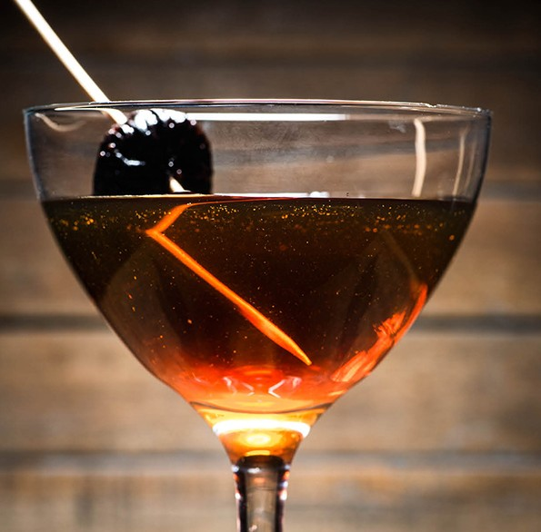 The Tailored Misfit cocktail, with Bulleit bourbon, Luxardo maraschino liqueur, and Carpano punt e mes, served with a bourbon-soaked fig