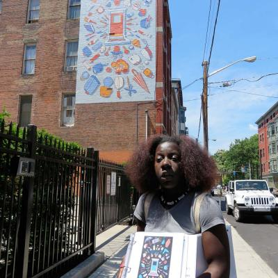 Kyra shows the group one of the proposed designs for the No Place Like Home mural at Tender Mercies