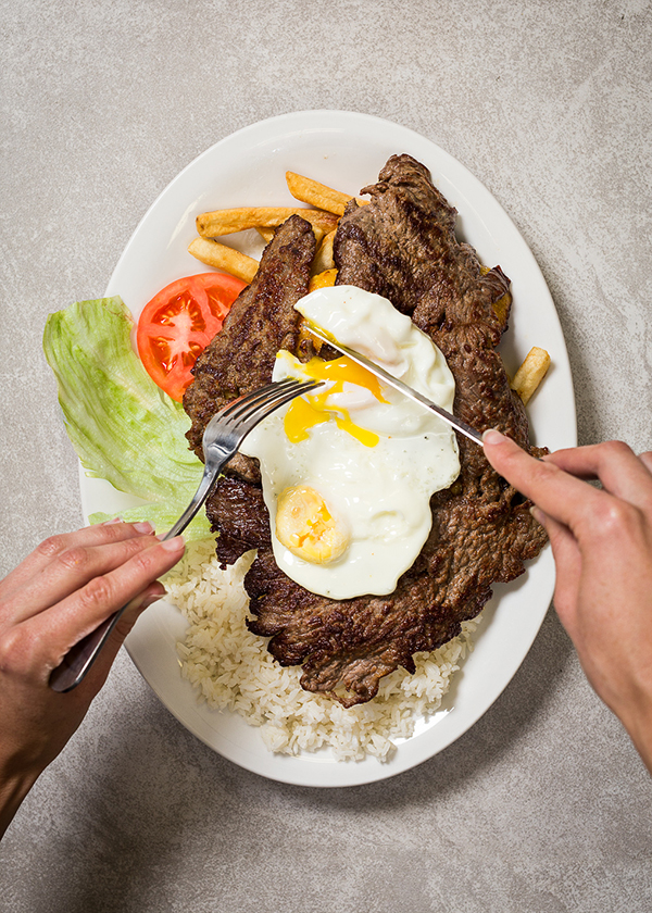 Bistek a la pobre (steak on top of french fries on top of rice with a fried egg)