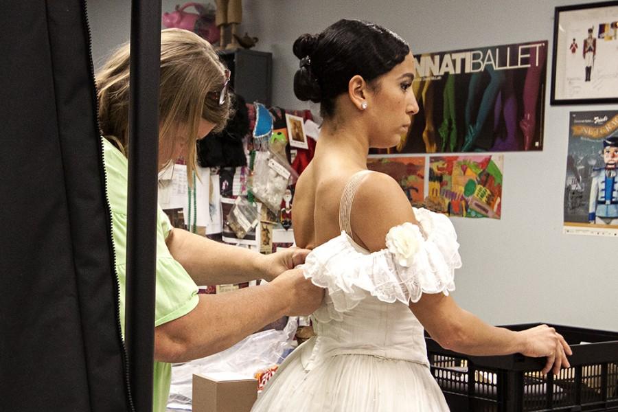 Wardrobe assistant Laura Hoffman fits a costume to soloist Maizyalet Velázquez