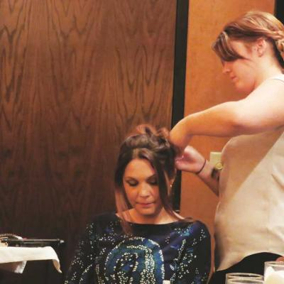 The hairstylist creates a pretty updo.