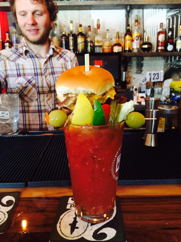 Yacht Club Bloody Mary: House mix, Stolichnaya Vodka, and citrus juice garnished with a pulled pork slider, bacon, and a smoked chicken wing.