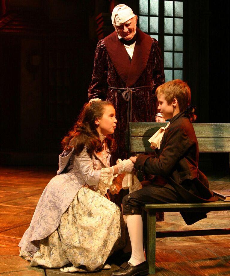 Corri Elizabeth Johnson (Fan) greets Evan Martin (Boy Scrooge) as Joneal Joplin (Ebenezer Scrooge) looks on in the 2004 production.