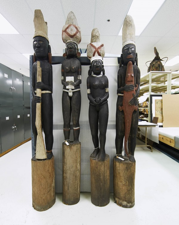 Four corner posts, some more than seven feet tall, that supported a canoe house on New Georgia Island. The book and rifle testify to earlier visits by missionaries.