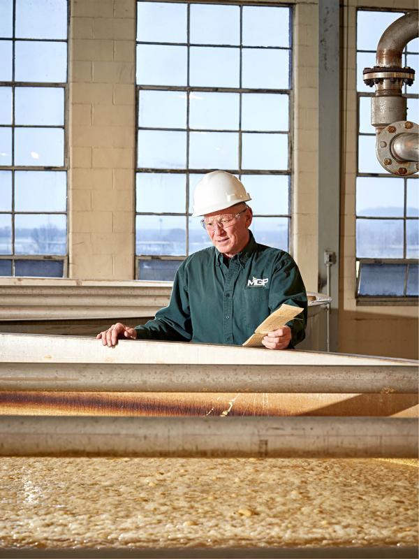 Master Distiller Greg Metze checks a tank full of fermenting mash