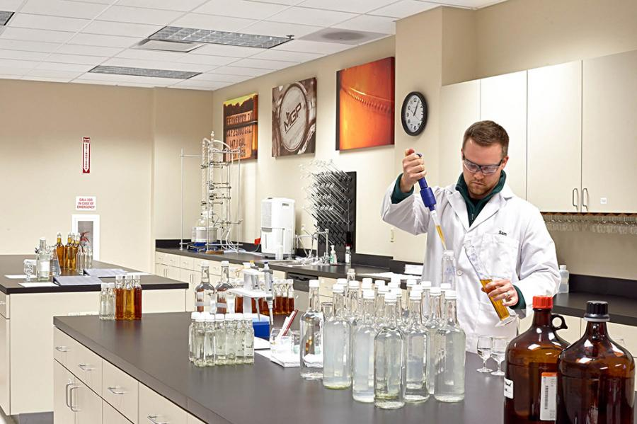 Lab Technician Sam Schmeltzer takes a sample