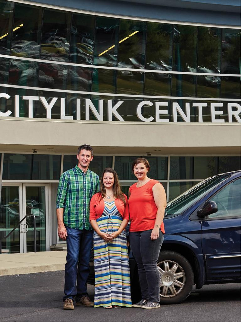 Tracy Summers (center) stands in front of her Chrysler Town & Country with Changing Gears founder Joel Bokelman and program director Katie Frazier.