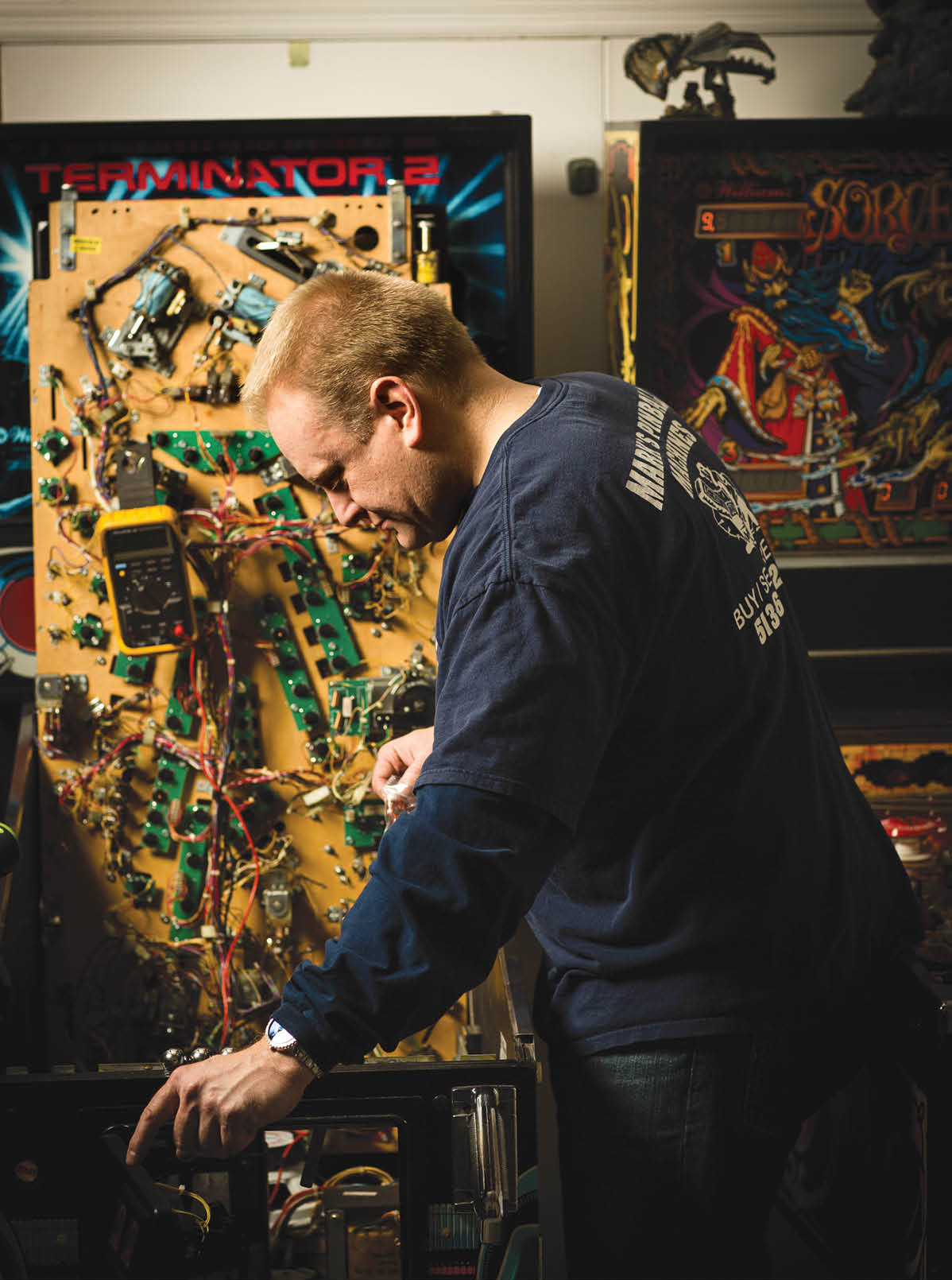 Mark Combs, owner of his own pinball repair shop, inspects the circuitry inside Terminator 2