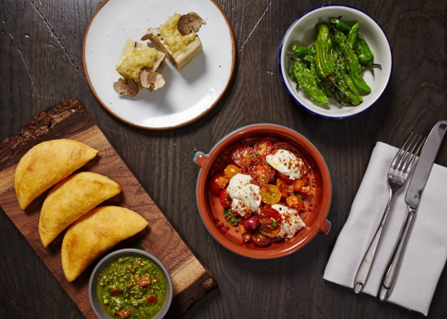 A selection of small plates (clockwise from top) Spanish omelette, blistered shishito peppers, queso burrata with tomatoes and serrano ham, and beef short rib empanadas.