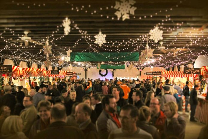 Holiday shoppers explore the ware underneath the heated tent at Germania Society's Christkindlmarkt.