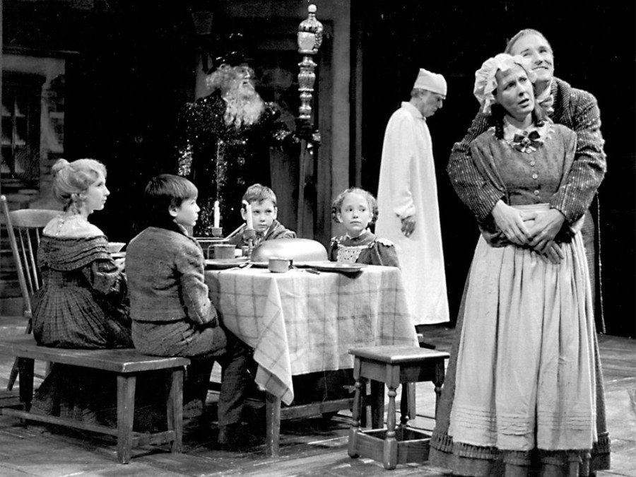 The Cratchit family in the 2000 production, left to right: Mary Jesse Price (Martha Cratchit), Dustin M. Hicks (Peter Cratchit), Adam Weinel (Tiny Tim), Regina Pugh (Mrs. Cratchit) and Bob Cratchit (Bruce Cromer). Background: Mark Mineart (Ghost of Christmas Present) and Joneal Joplin (Ebenezer Scrooge).