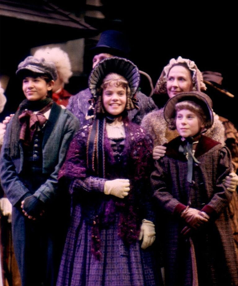 The 2002 production's finale, left to right: Dustin M. Hicks (Peter Cratchit), Sloan Thacker (Martha Cratchit) and McKenzie Miller (Belinda Cratchit), with Bruce Cromer as Bob Cratchit, and Regina Pugh as Mrs. Cratchit.