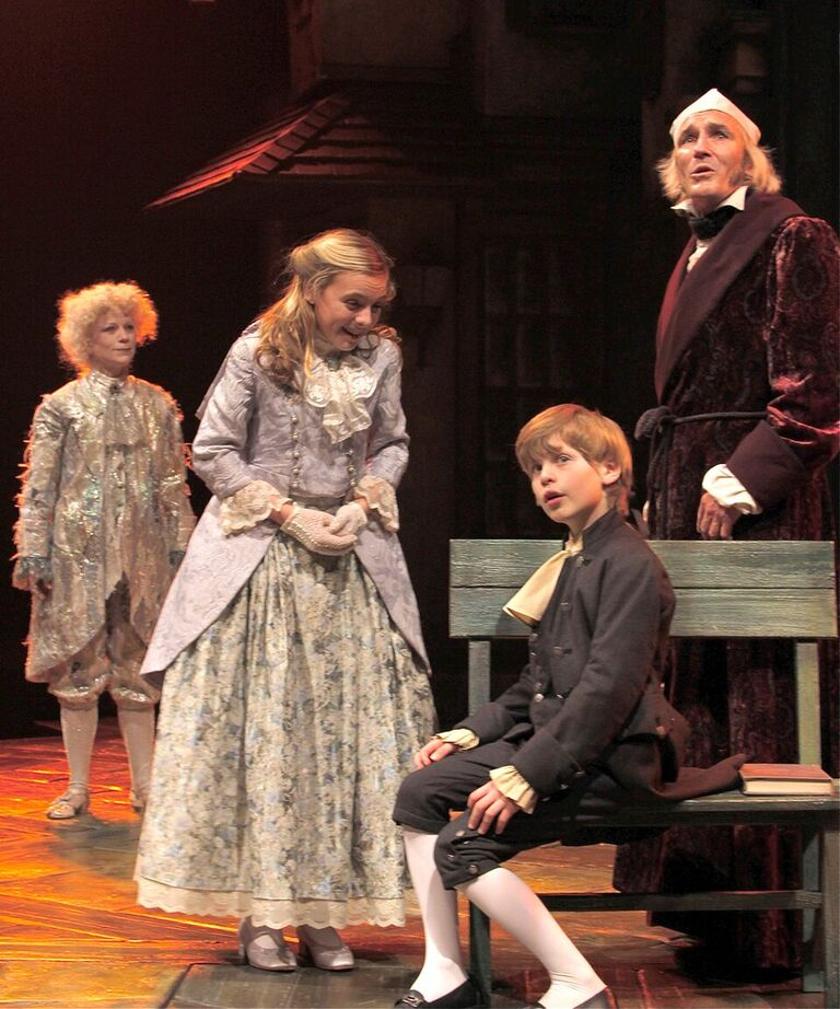 Allison Edwards (Fan, second from left) greets Ethan Verderber (Boy Scrooge, second from right) as Raye Lankford (Ghost of Christmas Past, left) and Bruce Cromer (Ebenezer Scrooge, right) observe in the 2013 production.