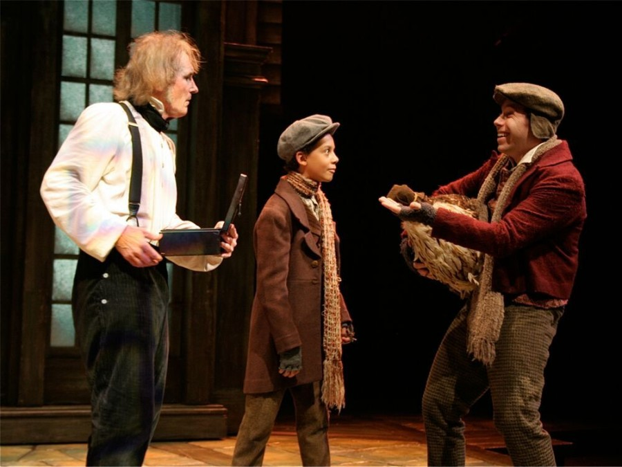 Bruce Cromer (Ebenezer Scrooge) and Javier Gresham (George) interact with the Poulterer (Matthew David Gellin) in the 2010 production.