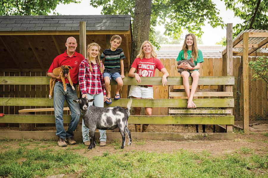 (Clockwise from top) The Slusher family—from left, Clay, Avery, Peyton, Erika, and Grayson—with Casper (the friendly goat!), the pup, and a chicken