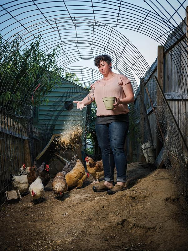 Megan Ayers scatters feed to the brood in her Sayler Park backyard.